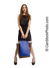 Model in black dress holding bags