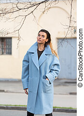 Model posing confidently in a blue coat with hre hand in he rpocket in the city