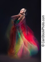 Model in colorful dress on black background