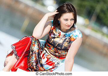 Model in dress posing on exterior set angled