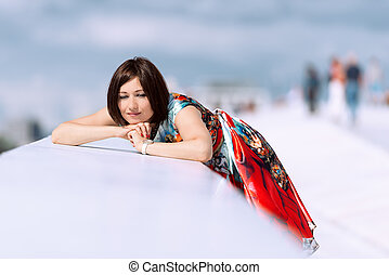 Model in dress posing on exterior set daydreaming