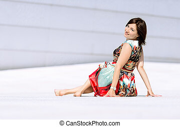 Model in dress posing on exterior set looking back