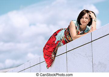 Model in dress posing on exterior set on a wall