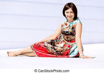 Model in dress posing on exterior set sitting looking