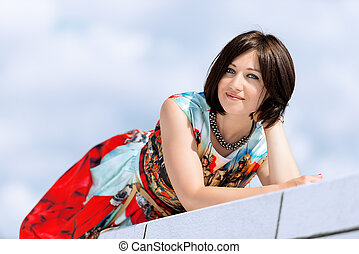 Model in dress posing on exterior set smiling looking into camer