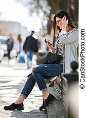 model in the middle of city with phone