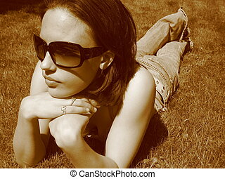 Model in the Sun - Attractive woman in sunglasses laying on ...
