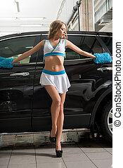 Model in uniform washing car at car wash service