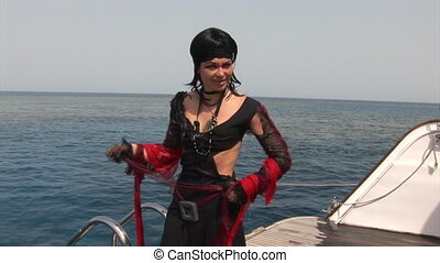Model in white costume of pirate on ship near water in Red Sea.