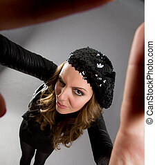 Attractive young female looking at viewer through hands