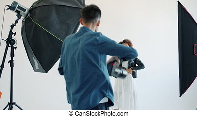 Model mixed race lady and photographer are working in studio during photo shoot, girl is wearing trendy clothing and make-up. People and advertising concept.