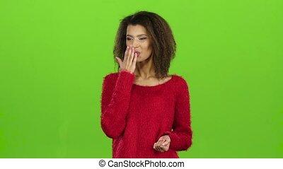 Model mulatto woman sends air kisses, green screen. Slow motion