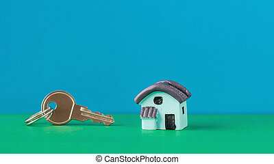 Model of a blue house with a key on a green Desk on blue background.