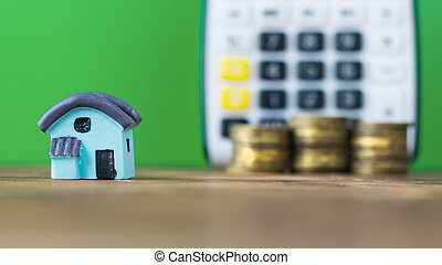 Model of a blue house with the coins on the background of the calculator.