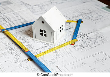 Model of a house on top of blueprints and architect tools