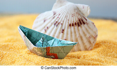 Model of a ship from a paper map on the sand and a seashell