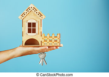 Model of a wooden house in the palm of your hand with keys on a blue background.