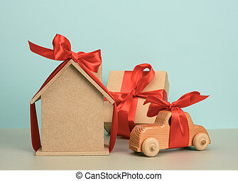 model of a wooden house tied with a red silk ribbon and a wooden car on a blue background, the concept of purchase