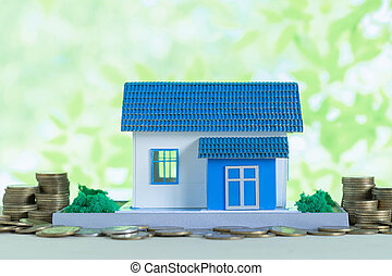 Model of house with coins on wooden table, saving money for buy home concept