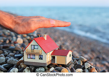 model of house with garage on stony beach in evening, Man\'s...