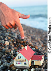 model of house with garage on stony beach in evening, Man\'s hand