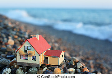 model of house with garage on stony beach in evening