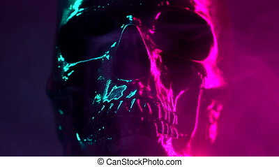 Model of human skull painted with black rotates on dark...