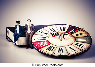 model of man sitting on organizer or planner with old clock
