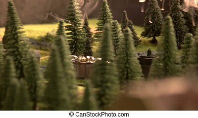 Model of railway freight train passing the forest.