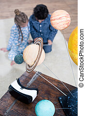 model of the solar system and Virtual reality headset on table with children behind