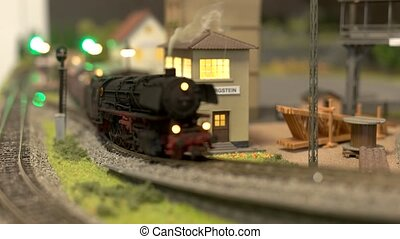 Model of train moving along railway station.