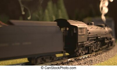 Model of vintage steam locomotive entering the tunnel.