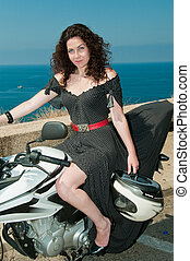Model on a motorcycle with helmet in hand against the sea