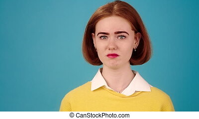 Young woman model in yellow knitted sweater performs sad emotions grimacing on blue studio stage slow motion close view