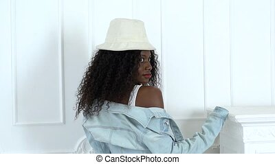 Model posing in a white studio she has red lips she is an african american. Slow motion