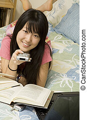 Model Release 363 Asian American teen watching television while doing homework