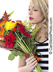 Model Released. Attractive Young Woman Holding a Bunch of Flowers