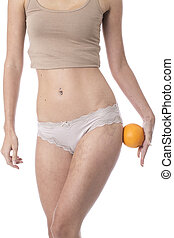 Model Released. Attractive Young Woman Holding an Orange to Her Thigh