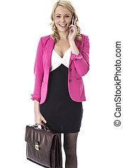 Model Released. Attractive Young Woman With a Briefcase and Mobile Telephone