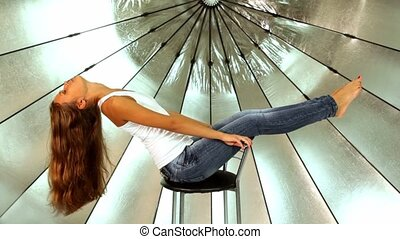 Model sits in photo studio, she lean back and extend legs