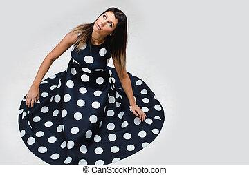 Model sitting looks up in a polka dot dress