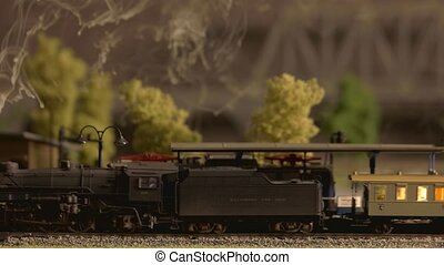 Model steam train moving through station close up.