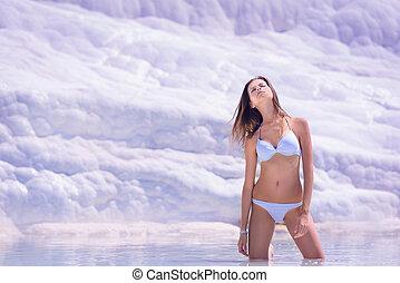 model sunbathing on white limestone