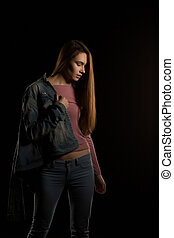 Model test for fashionable brunette woman in trendy outfit posing on a dark background