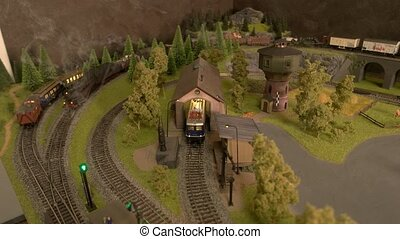 Model trains with steam moving on the railway.