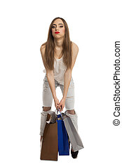 Model trying to lift shopping bags