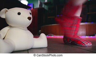 Model walking legs in soft slippers walk on floor in nightclub. Plush bear toy