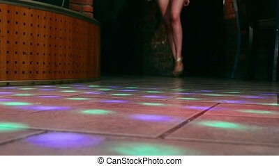 Model walking legs on high heels on floor. Runway fashoin show in nightclub.