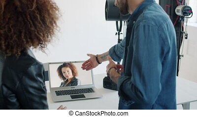 Model watching new photos talking to photographer in studio looking at laptop screen