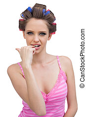 Model wearing hair curlers biting her finger sexily
